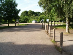 The path follows the timber bollards past the car park.