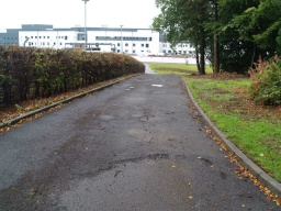 Follow the path round towards the hospital.