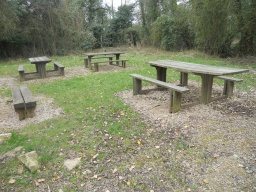 The picnic bench in the foreground has a lengthened tabletop which makes it more accesible to wheechair users. Access to the  bench is over uneven stone surfacing.