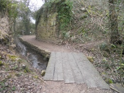 Railway sleepers bridge the stream. The path next to the stream narrows to 1.2m and no safety rail is present.