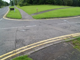 There is a slight kerb drop as the path crosses the entrance road to the water sports centre.