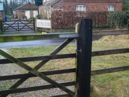 The latch to the gate should be reachable from both sides. The gate opens towards the road.