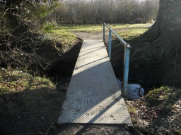 The footbridge has a step level rise and the handrail is only on one side.
