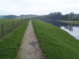 The crushed stone path runs along the river bank before linking to the return farm track through the fields.