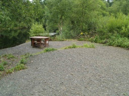 There is an accessible picnic bench by a potential fishing spot.