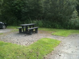 There are picnic benches located next to the car park