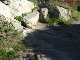 There is a rocky uneven area as the path crosses the headland. There is a resting point in the rock.