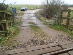 There is a gradient sampled at about 14% (1:7) leading to the railway with some large loose stones and a small step before the level crossing boarding.