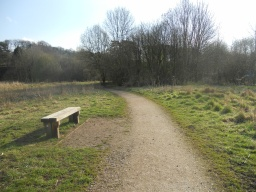 The first rest area is approximately 100m along the path, offering pleasant views across the meadows.