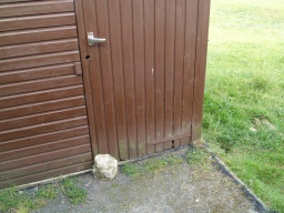 The door is held closed by a rock that has to be moved to open the door outwards.