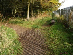 There is a seat at the top of the rise along the side of the railway line fence.
